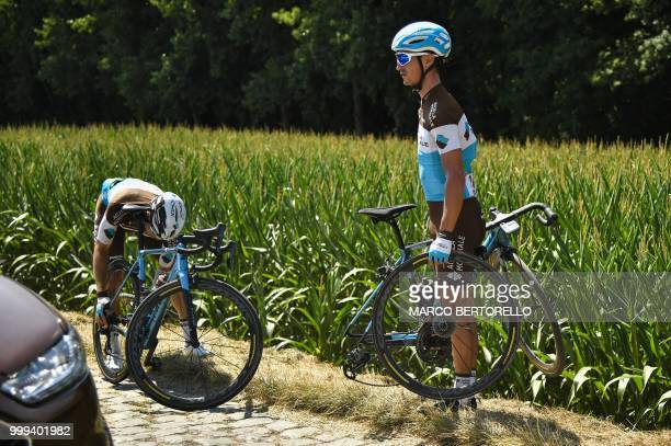 France's Alexis Vuillermoz stands by the stage's first cobblestone section after handing a wheel to France's Romain Bardet who suffered a puncture...