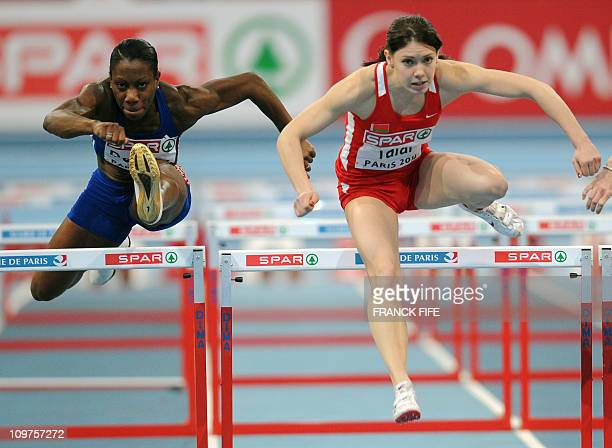 France's Alice Decaux and Belarus's Alina Talay compete in the 60m hurdles first round women's event of the European athletics indoor championships...