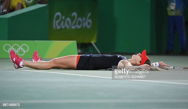 France's Alize Cornet lies on the court during her women's second round singles tennis match against USA's Serena Williams at the Olympic Tennis...