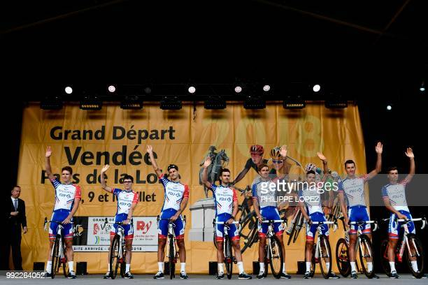 France's Arnaud Demare and riders of France's Groupama - FDJ cycling team wave on stage during the team presentation ceremony on July 5, 2018 in La...
