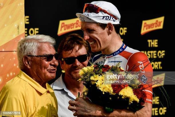 France's Arnaud Demare talks with former French rider Raymond Poulidor as he celebrates on the podium after winning the 18th stage of the 105th...