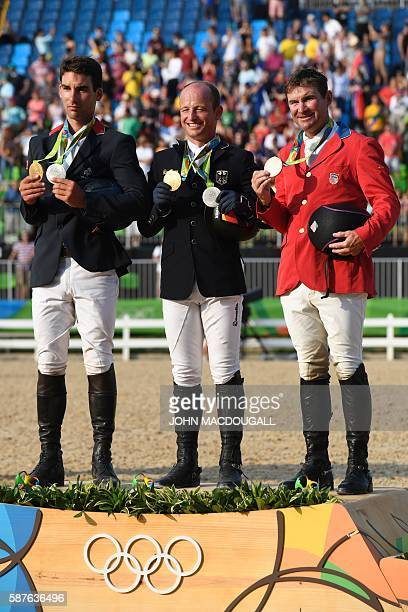France's Astier Nicolas, Germany's Michael Jung and USA's Phillip Dutton celebrate on the podium of the Eventing's Jumping of the Equestrian during...