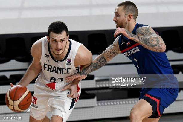 France's Axel Julien fights for the ball with Britain's Ashley Hamilton during the FIBA EuroBasket 2022 qualifier basketball match between France and...