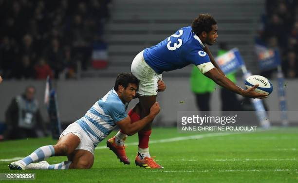 France's back row Benjamin Fall passes the ball as he is tackled by Argentina's centre Matias Orlando during the international rugby union test match...