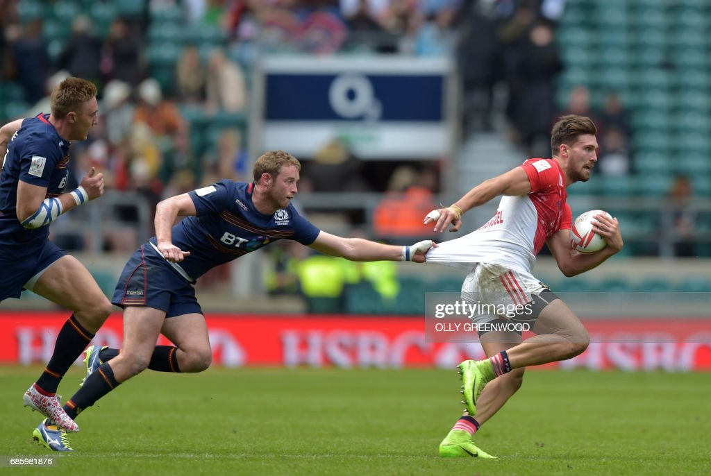 France's Bastien Berenguel (R) is grabbed by Scotland's Dougie Fife during the group stage match of the World Rugby Sevens Series - London, rugby union tournament between France and Scotland, at Twickenham in south west London on May 20, 2017. France beat Scotland 17-12. /