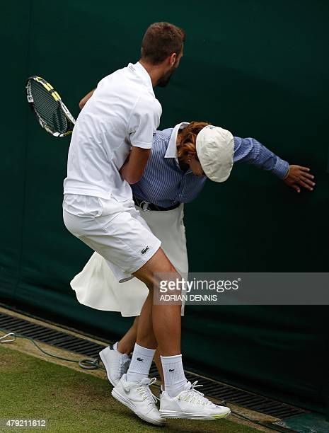 France's Benoit Paire collides with a line judge after stretching to play a return shot to Spain's Roberto Bautista Agut during their men's singles...