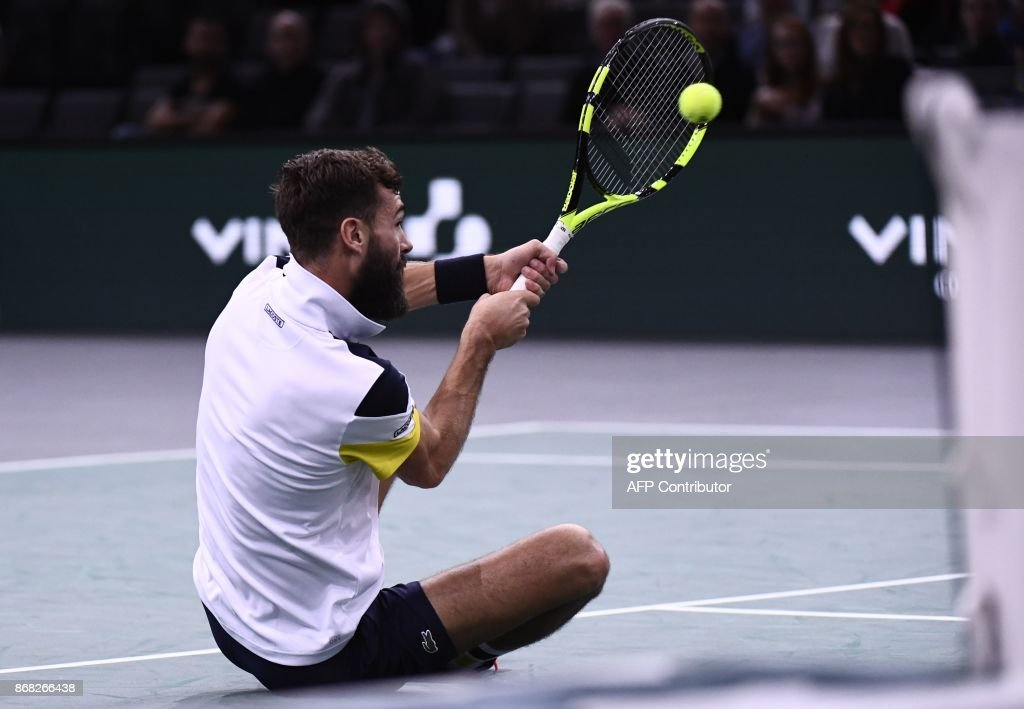 France's Benoit Paire returns the ball as he falls during his first round match against France's Richard Gasquet at the Paris Masters ATP tennis Open on October 30, 2017 in Paris. /