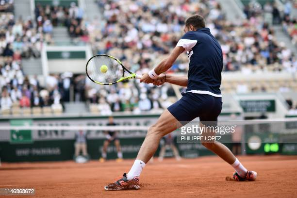 France's Benoit Paire returns the ball to France's PierreHugues Herbert during their men's singles second round match on day four of The Roland...