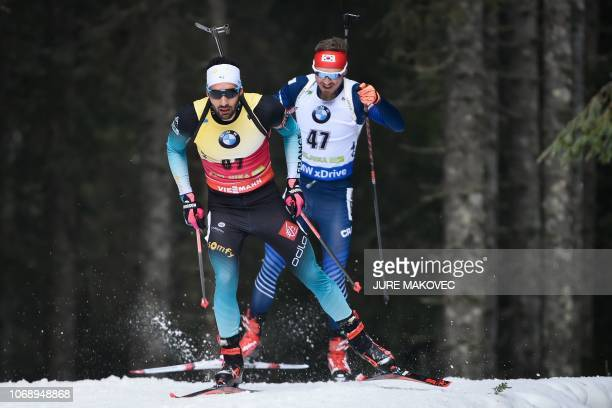 France's biathlete Martin Fourcade competes followed by South Korea's biathlete Timofei Lapshin during the IBU Biathlon World Cup Men's 20km...