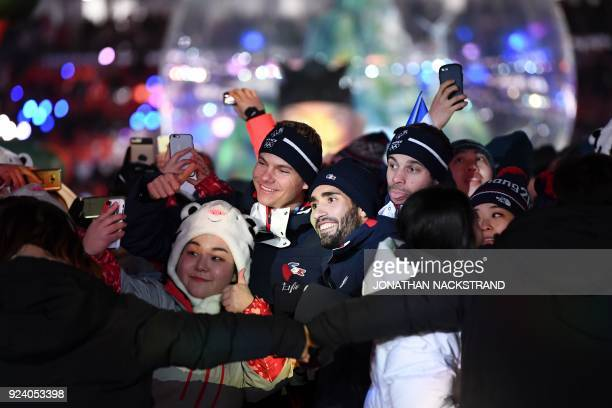 TOPSHOT France's biathlon champion Martin Fourcade poses for a selfie with fellow athletes and volunteers during the closing ceremony of the...