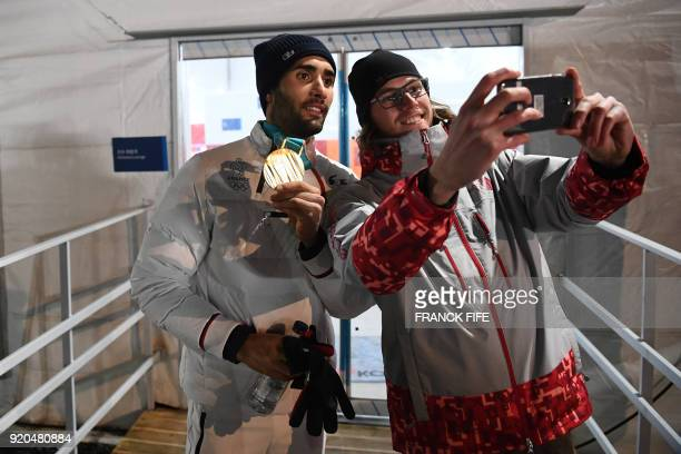 France's biathlon double gold medallist Martin Fourcade poses for a selfie with a volunteer as he leaves the Athletes' Lounge after the medal...