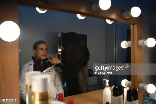 France's biathlon gold medallist Anais Bescond gets ready backstage at the Athletes' Lounge during the medal ceremonies at the Pyeongchang Medals...