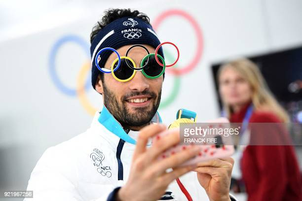 France's biathlon gold medallist poses for a selfie with sunglasses shaped like Olympic rings backstage at the Athletes' Lounge during the medal...