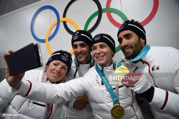 France's biathlon gold medallists Marie Dorin Habert, Simon Desthieux, Anais Bescond and Martin Fourcade pose for a selfie with their medals in front...