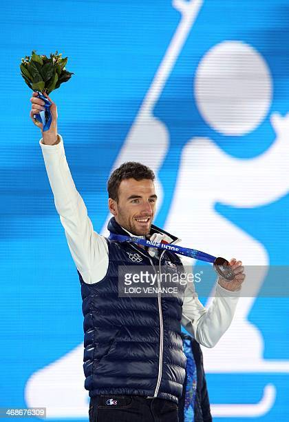France's bronze medalist Jean Guillaume Beatrix poses during the Men's Biathlon 125 km Pursuit Medal Ceremony at the Sochi medals plaza during the...