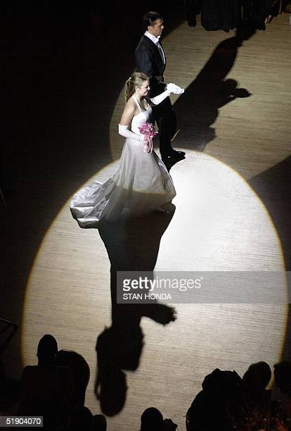 STORY USASOCIETE BY CATHERINE HOURS Frances Cain of Wilmington NC walks with her escort in the spotlight as she is presented at the International...