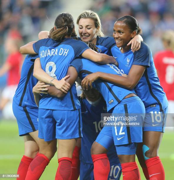 France's Camille Abily celebrates with teammates after scoring a goal during the women's friendly football match between France and Norway on July 11...