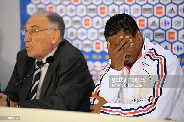 France's captain Patrice Evra reacts next to JeanPierre Escalettes president of the French Football Federation during a press conference in Knysna on...