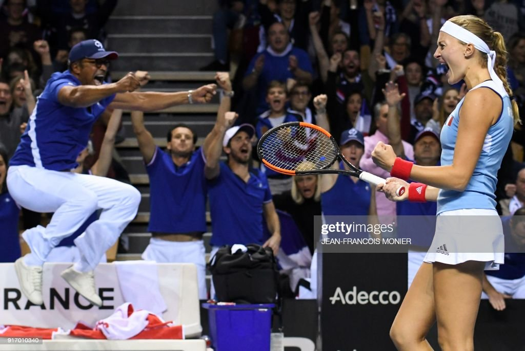 France's captain Yannick Noah (L) and France's Kristina Mladenovic (R) react after a point during the Fed Cup World group first round tennis double match with France's Kristina Mladenovic and Amandine Hesse against Belgium's Kirsten Flipkens and Elise Mertens, in Mouilleron-le-Captif, northwestern France, on February 11, 2018. France made the semi-finals for the third time in four years when Kristina Mladenovic won her third point of the weekend by teaming with world number 228 Amandine Hesse to beat Kirsten Flipkens and Elise Mertens 6-4, 2-6, 6-2 in the deciding doubles. / AFP PHOTO / Jean-Francois MONIER