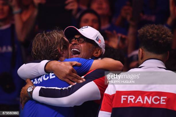 TOPSHOT France's captain Yannick Noah celebrates Lucas Pouille after he won his singles rubber 5 match against Belgium's Steve Darcis at the Davis...