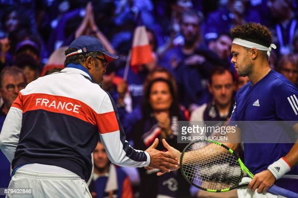 France's captain Yannick Noah taps hand with France's Jo-Wilfried Tsonga during the singles rubber 4 of the Davis Cup World Group final tennis match...