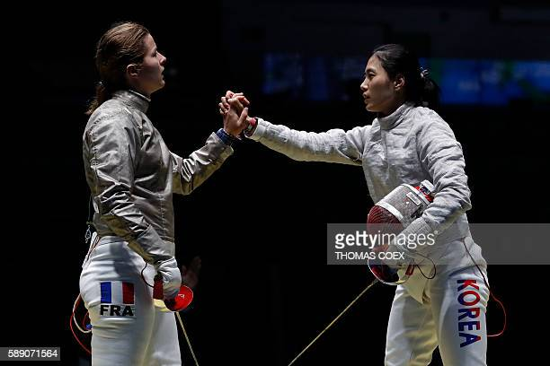 France's Cecilia Berder shakes hands with South Korea's Kim Jiyeon after losing the women's classification 58 bout between South Korea and France as...