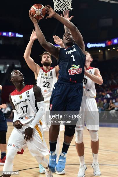 France's center Kevin Serephin tries to scoce a basket next to Germany's forward Daniel Theis and guard Dennis Schroder during FIBA Eurobasket 2017...