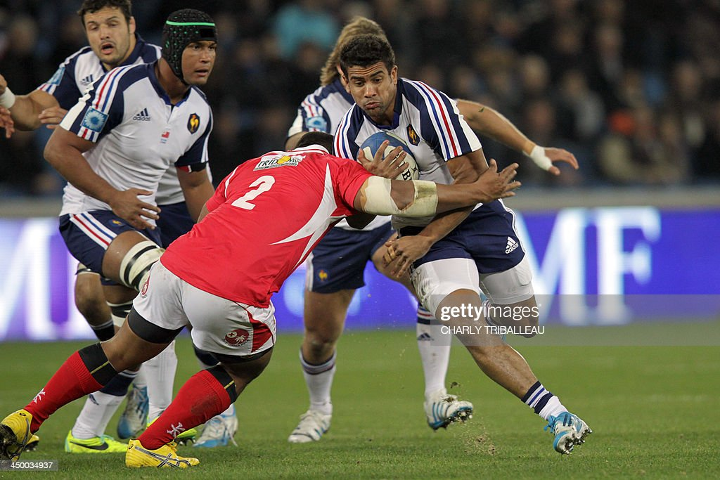 Frances center Wesley Fofana (R) avoids a tackle during the rugby union test match France vs Tonga on November 16, 2013 at the Oceane stadium in Le Havre, northwestern France.