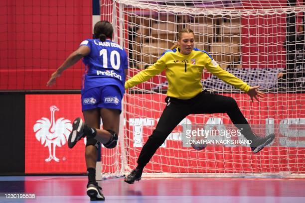 France's Centre back Grace Zaadi scores against Croatia's Goalkeeper Lucija Besen during the semi-final match between France and Croatia of the 2020...