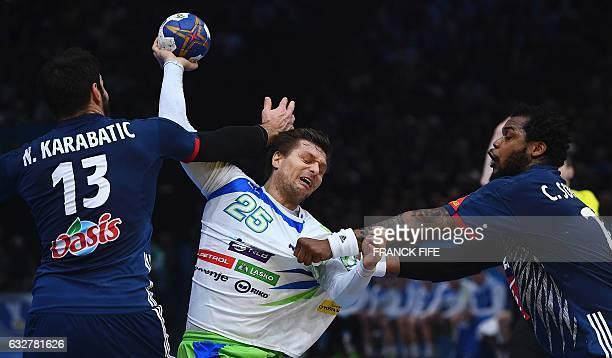 TOPSHOT France's centre back Nikola Karabatic and France's pivot Cedric Sorhaindo hold back Slovenia's centre back Marko Bezjak during the 25th IHF...