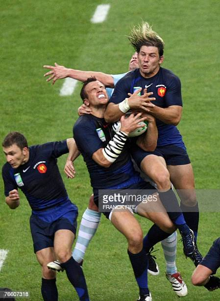 France's centre Damien Traille and France's fullback Cedric Heymans try to grab the ball during the Rugby Union World Cup opening match France v....