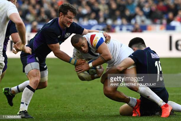TOPSHOT France's centre Gael Fickou is tackled by Scotland's flyhalf Peter Horne and Scotland's fullback Blair Kinghorn during the Six Nations rugby...