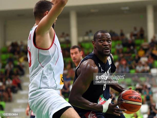 France's Charles Kahudi fights for the ball with Bulgaria's Pavel Marinov during the 2019 FIBA European qualifying basketball match between Bulgaria...