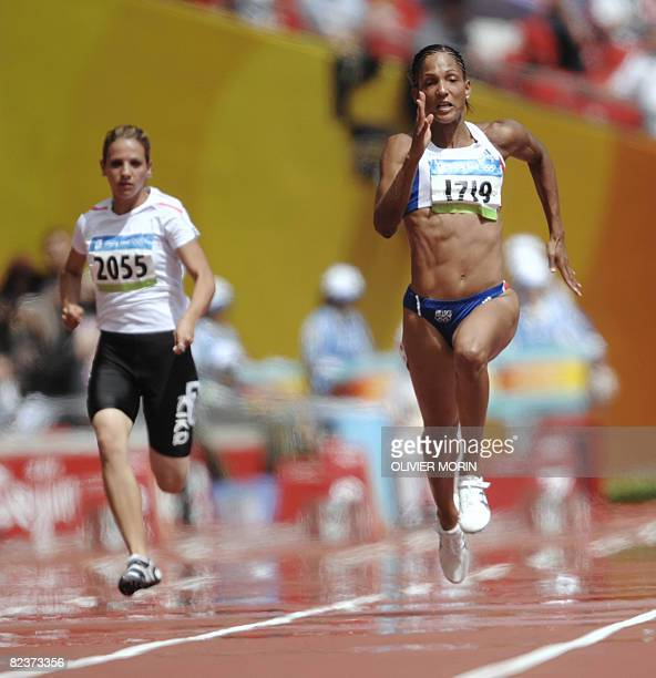 France's Christine Arron and Iraq's Dana Hussein Abdulrazak compete during the women's 100m heat 2 at the 'Bird's Nest' National Stadium as part of...