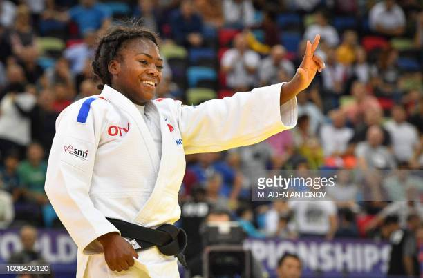 France's Clarisse Agbegnenou shows three fingers for her third gold medal after winning the women under 63kg category of the 2018 Judo World...