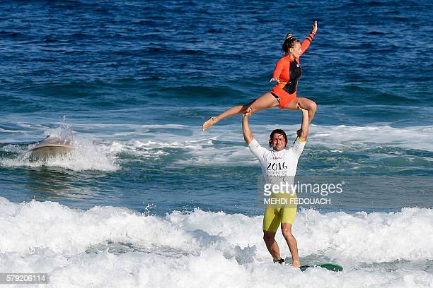 France's Clement Cetran and Dhelia Birou Cetran compete in the International Tandem Surfing Championship on July 23 2016 in Biscarrosse / AFP / MEHDI...