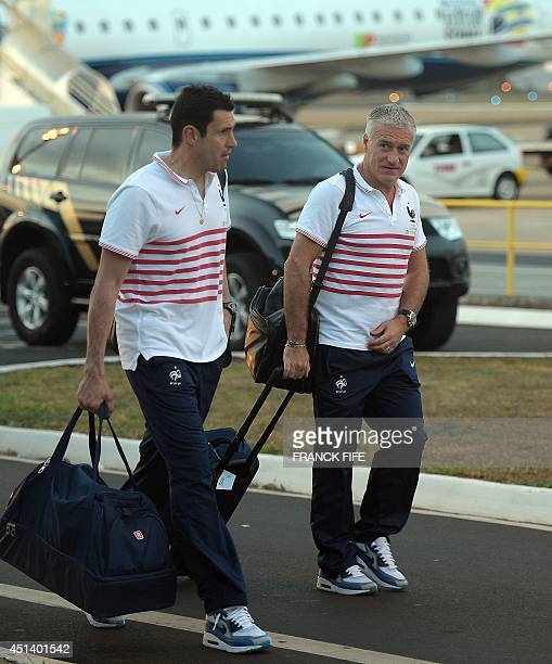 France's coach Didier Deschamps and a staff member walk at the Ribeirao Preto airport before boarding a plane to Brasilia on June 28 during the 2014...