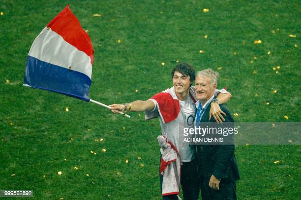 TOPSHOT France's coach Didier Deschamps celebrates with his son Dylan Deschamps waving the French national flag during the trophy ceremony after...