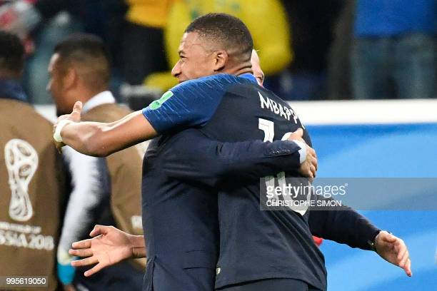 France's coach Didier Deschamps hugs France's forward Kylian Mbappe at the end of the Russia 2018 World Cup semifinal football match between France...