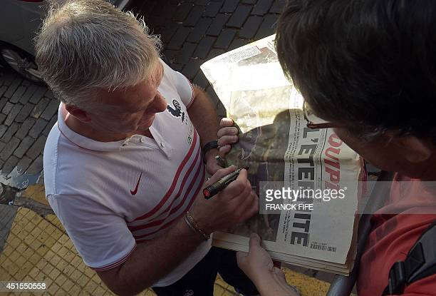 France's coach Didier Deschamps signs an autograph before a press conference at a theater in Ribeirao Preto on July 1 during the 2014 FIFA World Cup...