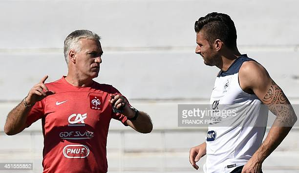 France's coach Didier Deschamps speaks with forward Olivier Giroud, during a training session at the stadium Santa Cruz in Ribeirao Preto on July 1...