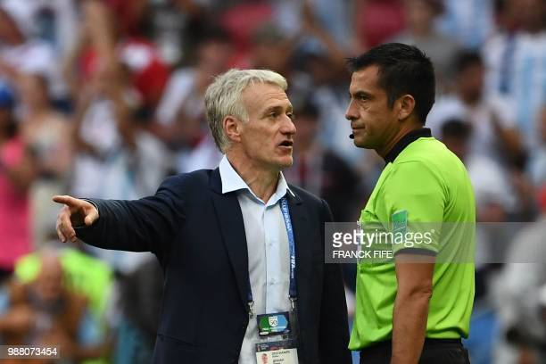 France's coach Didier Deschamps talks to Irani referee Alireza Faghani during the Russia 2018 World Cup round of 16 football match between France and...