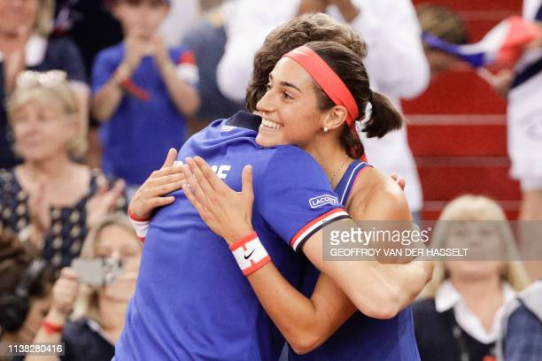 France's coach Julien Benneteau congratulates France's Caroline Garcia as she celebrates after winning against Romania's Mihaela Buzarnescu at the...