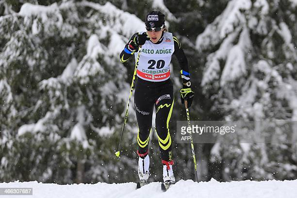 France's Coraline Hugue competes during the FIS Ski World Cup Ladies' 10 Km Individual Classic race on February 1 2014 in Dobbiaco Norway's Marit...