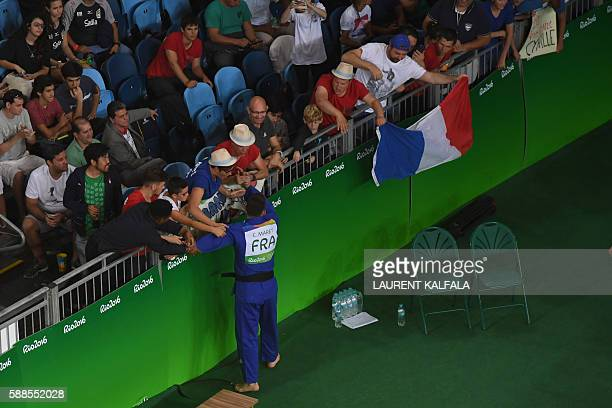 France's Cyrille Maret celebrates with France supporters after defeating Germany's KarlRichard Frey during their men's 100kg judo contest bronze...