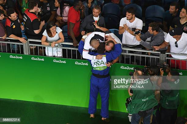 France's Cyrille Maret celebrates with relatives after defeating Germany's KarlRichard Frey during their men's 100kg judo contest bronze medal A...