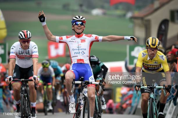France's David Gaudu raises his arm after winning ahead of Slovenia's Primoz Roglic the 3rd stage 160 km loop from Romont to Romont at the Tour de...