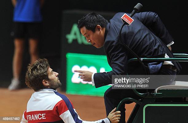 France's Davis Cup team captain Arnaud Clement argues with umpire James Keothavong during the tennis match between France's Richard Gasquet and...