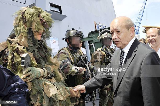 France's Defence Minister JeanYves Le Drian shakes hands with members of the French Navy commando Hubert during his visit on board of the French Navy...