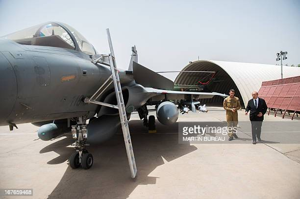 France's Defence Minister JeanYves Le Drian speaks with a Rafale fighter aircraft pilot during his visit of French troops of the Frenchled Operation...